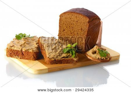 Fresh pate on bread on wooden board isolated on white