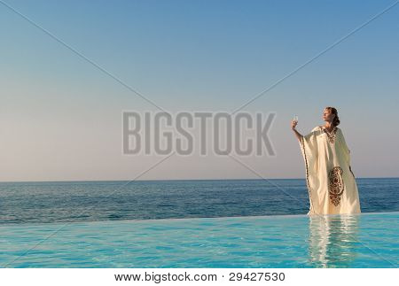 Greek Style Woman Stand On The Edge Of Infinity Pool