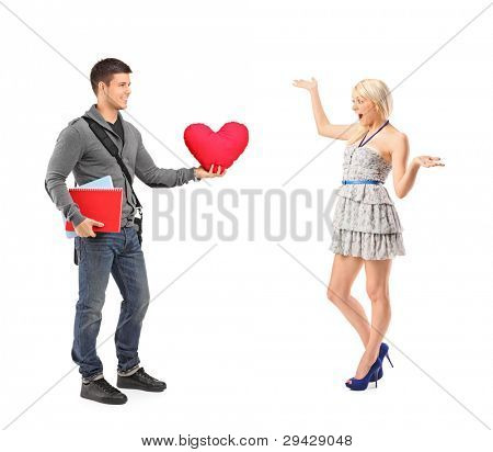 School boy presenting a red heart to an astonished female isolated on white background