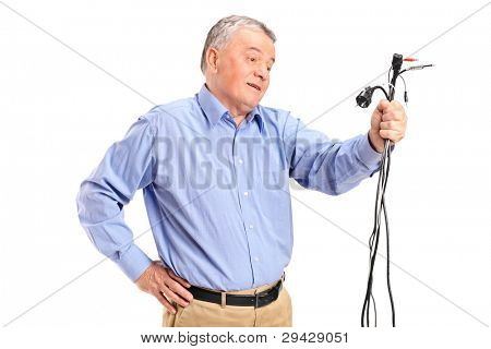 Confused senior holding electronic cables isolated on white background