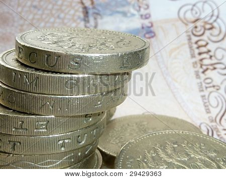 Stack of UK coins resting on banknote