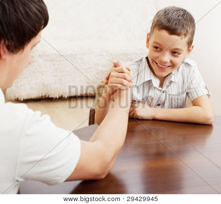 Father and son arm wrestling. Dad play with child