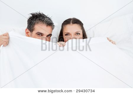 Couple caught in the act hiding in bed behind white sheets