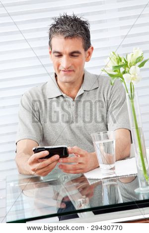 Elderly man looking at his smartphone in restaurant