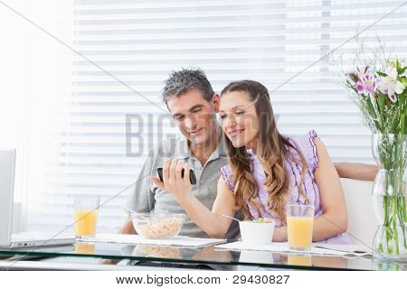 Happy couple with laptop and smartphone at breakfast table