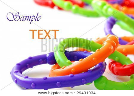 Brightly colored plastic chain links - a classic baby toy and teething ring also used to attach toys to stroller - on white background with copy space.  Macro with shallow dof.