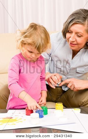 Granddaughter with grandmother play making hand-prints painting at home
