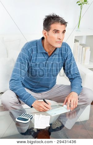 Senior man signing check on living room table