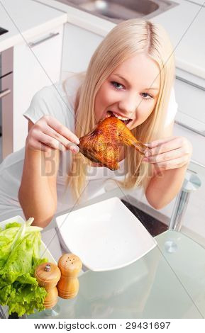 beautiful young blond woman eating chicken in the kitchen at home