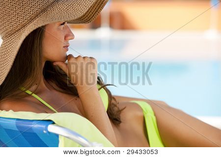 Beautiful young woman lying on deckchair by swimming-pool