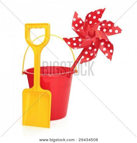 Toy windmill with beach bucket and spade in red and yellow colours isolated over white background.