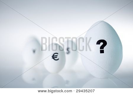 Close-up of big white egg with question mark on it among other eggs