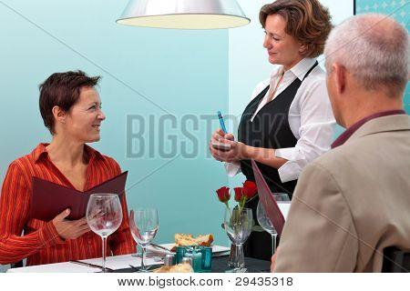 Foto de uma garçonete que tendo uma ordem de alimentos de um casal maduro, jantar em um restaurante