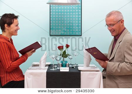 Photo of a mature couple sitting in a restaurant reading the menu