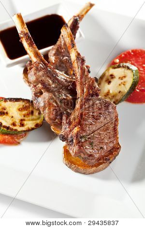 Roasted Lamb Chops on Potato with Tomato and Zucchini Garnished with Sauce