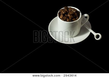 White Espresso Cup And Saucer Containing Coffee Beans