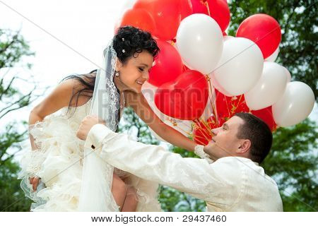 A groom holding a  bride with the red and white balloons