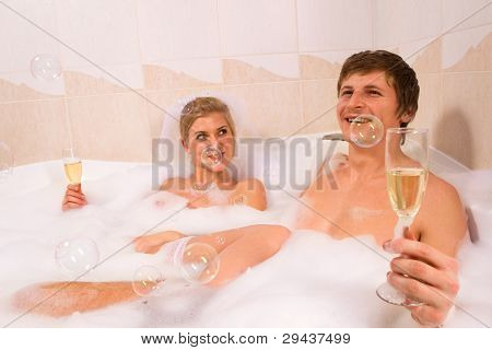 A young beautiful couple is enjoying a bath with champagne in a glass and looking at bubbles that are floating in the air