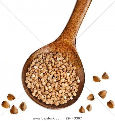 buckwheat groats in a wooden spoon  Isolated on white background