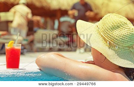 Woman enjoying drink on the edge of the swimming pool