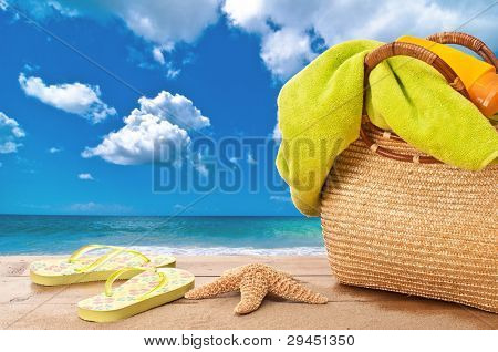 Beach bag with towel and sunblock overlooking the ocean