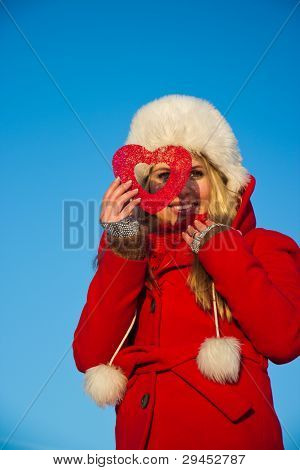 Woman In Red Coat Looking Through Heart Shape