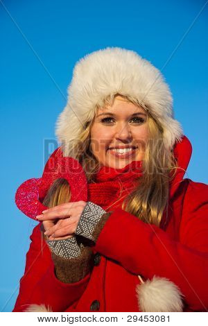 Woman In Red Coat Holding Heart Shape