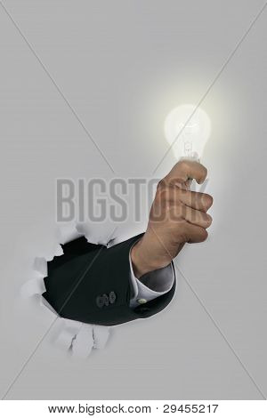 Businessman Hand Breaking Through A Paper Wall Holding Light Bulb