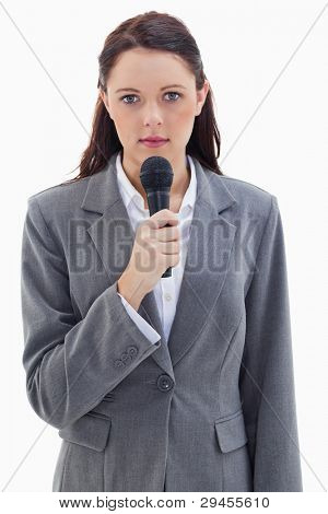Close-up of a serious businesswoman holding a microphone against white background