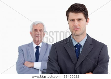 Close up of serious businessman with his mentor behind him against a white background