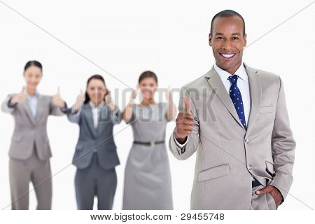 Happy businessman with a hand in his pocket and approving with co-workers in the background with thumbs up