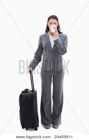 Businesswoman with a suitcase drinking a coffee against white background