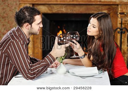 Couple Holding Glasses Of Wine And Cheers