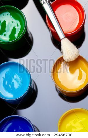 Paint buckets with paintbrush over dark background