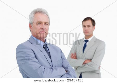 Serious tradesmen with arms folded against a white background