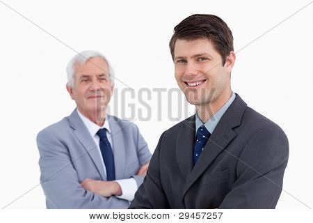 Close up of smiling businessman with his mentor behind him against a white background