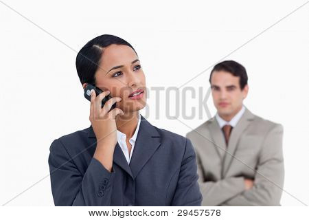 Saleswoman with colleague behind her listening closely to caller against a white background