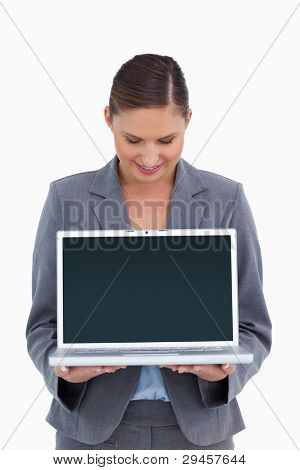 Smiling tradeswoman looking down at her laptop against a white background