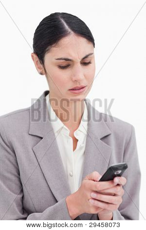 Close up of businesswoman confused by text message against a white background