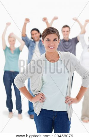 Close-up of a woman with her hands on her hips with people behind raising their arms against white background