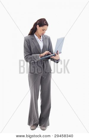 Businesswoman standing and typing on a laptop against white background
