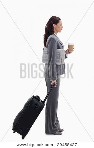 Profile of a businesswoman with a suitcase, a newspaper and a coffee against white background