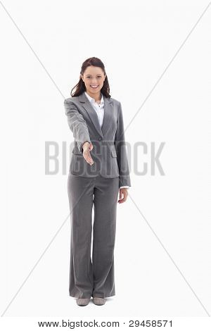 Businesswoman smiling and holding out her hand against white background