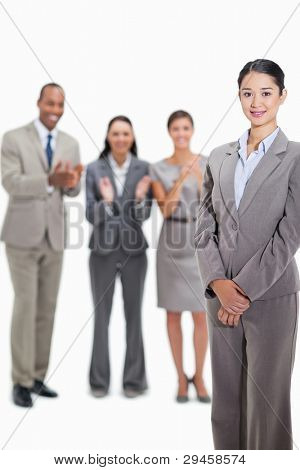 Close-up of a businesswoman smiling with co-workers applauding and looking at her in the background
