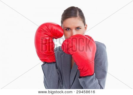 Tradeswoman with boxing gloves in defensive position against a white background