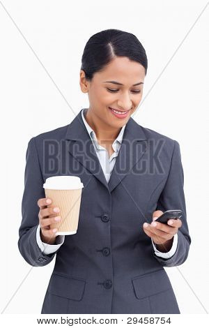 Close up of saleswoman with paper cup reading text message against a white background
