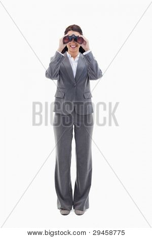 Businesswoman smiling and looking through binoculars against white background