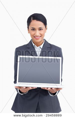 Close up of smiling saleswoman presenting screen of laptop against a white background
