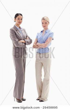 Two serious women crossing their arms against white background