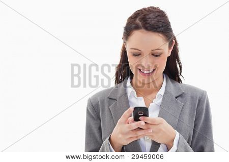 Close-up of a businesswoman smiling and writing a text message against white background